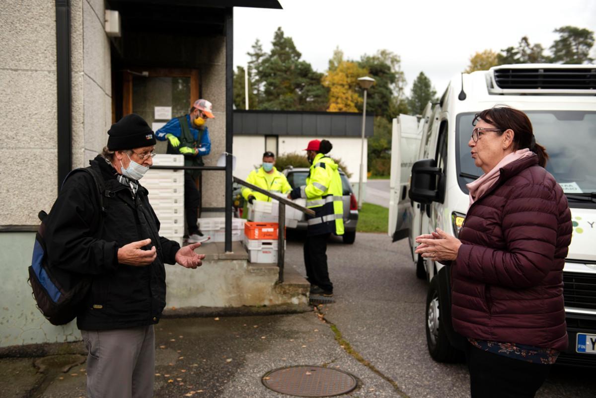 Vahti ry:n puheenjohtaja Tiina Tuomela juttelemassa yhdistyksen ruokajakelusta apua saavan Kaken kanssa. Takana Vantaan yhteisen pöydän auto tuo ruokatoimitusta lajiteltavaksi.